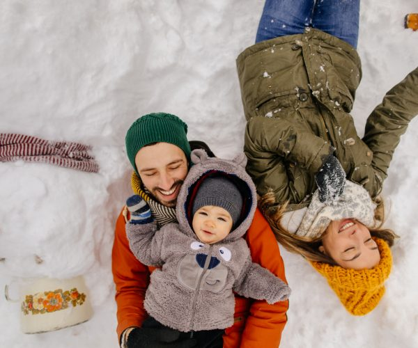 Portrait of a little boy and his parents proudly posing with a Snowman they have made together