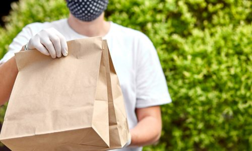 Courierin white hold go box food, delivery service, Takeaway restaurants food delivery to home door. Stay at home safe lives from coronavirus COVID-19 outbreak. Contactless delivery service under quarantine.