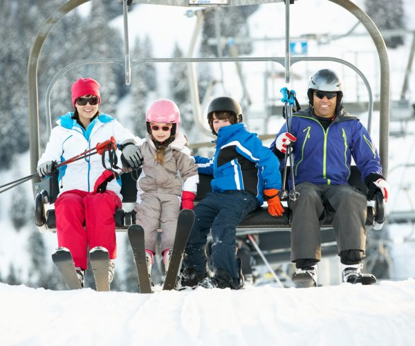 Family Getting Off chair Lift On Ski Holiday In Mountains Holding Ski Equipment Smiling